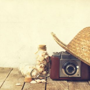 Summer or vacation concept. Straw hat with old vintage camera an